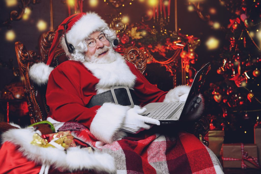 A portrait of Santa Claus sitting at his home with a laptop.