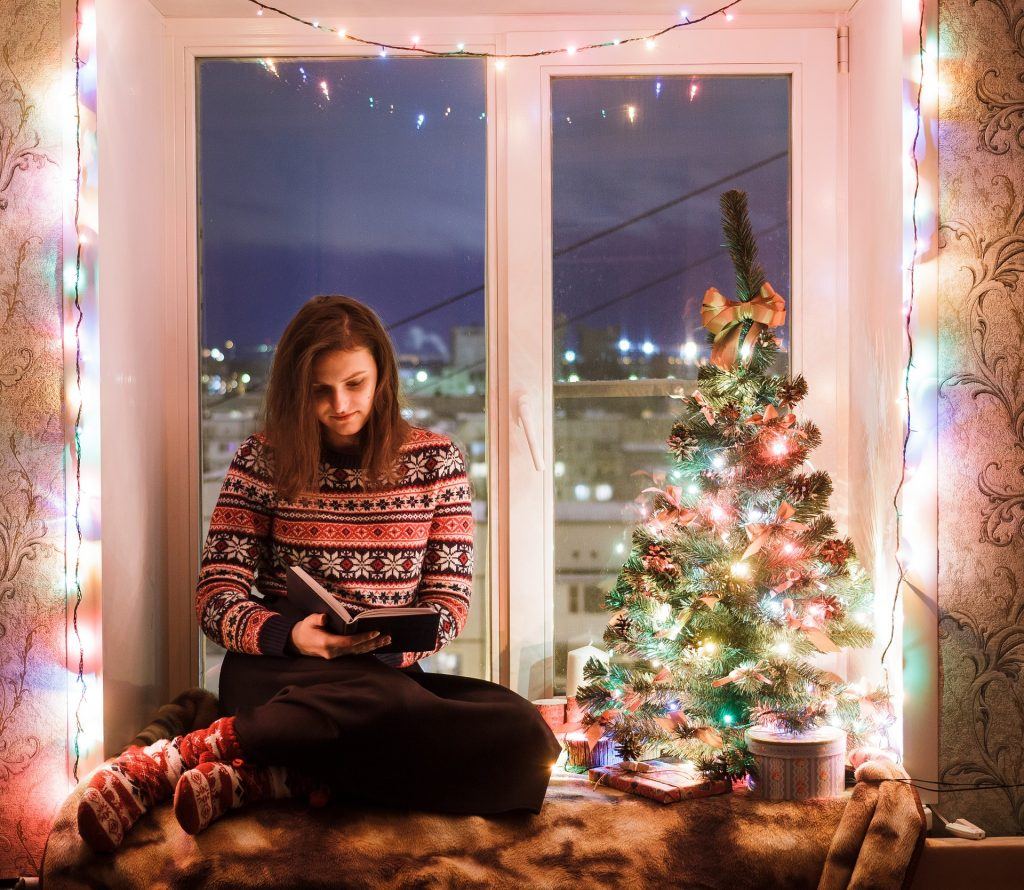 woman reading a book in a window seat next to a Christmas tree