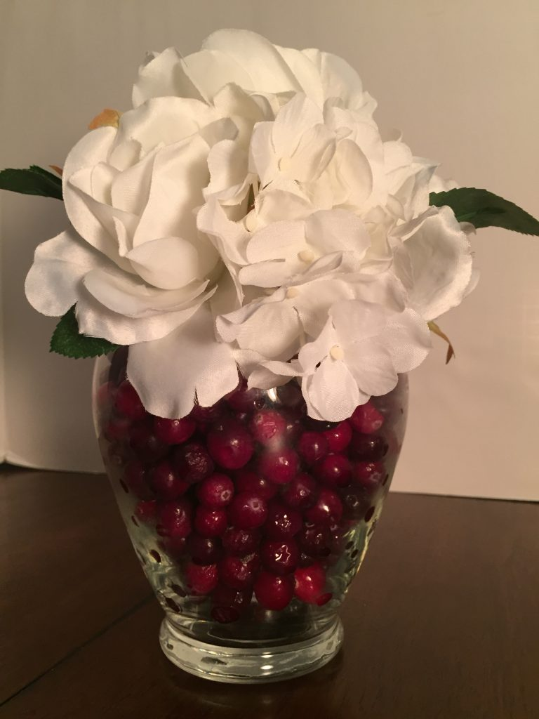 white flowers in vase with cranberries as filler
