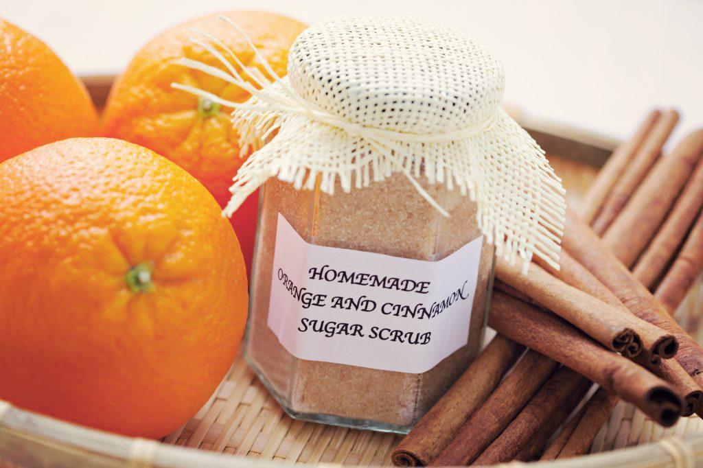 oranges, cinnamon sticks, and jar of homemade sugar scrub