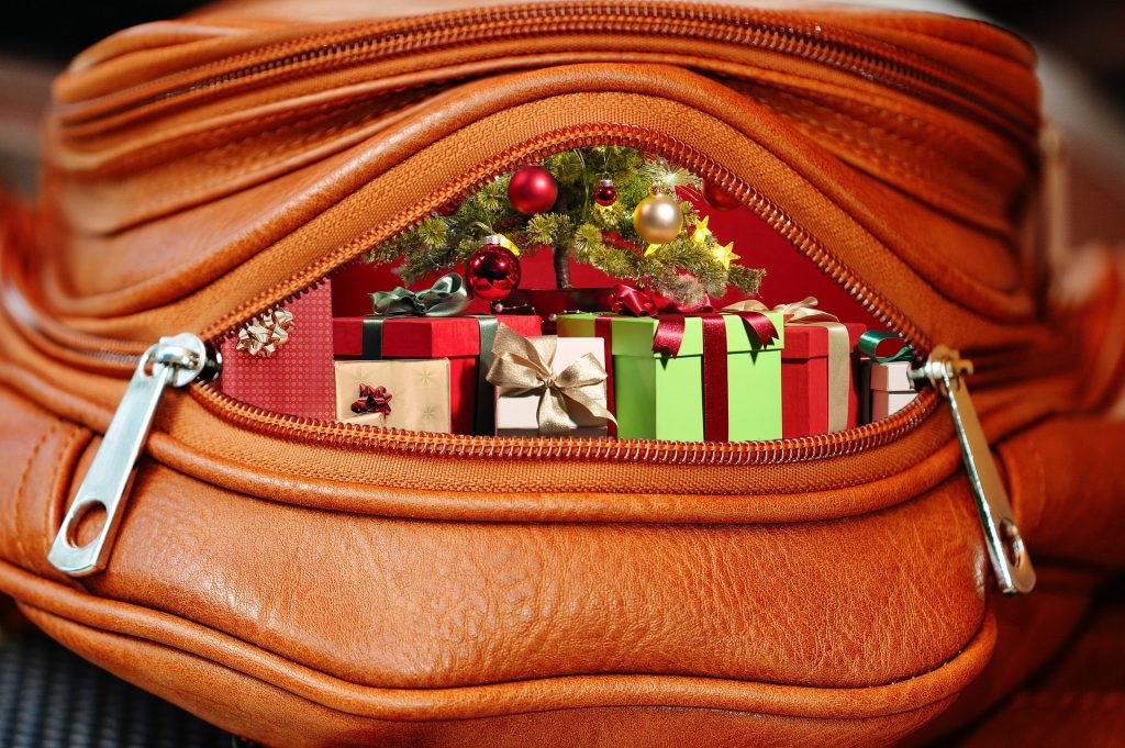 image of a brown leather purse filled with red and green wrapped gifts