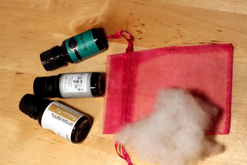 bottles of essential oils and fragrance oils with a mesh bag and cotton stuffing