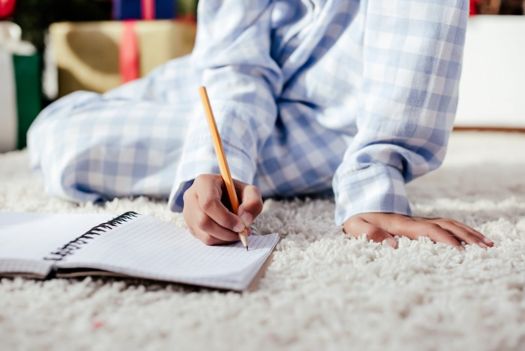 Woman in pajamas sitting on a white rug writing in a journal