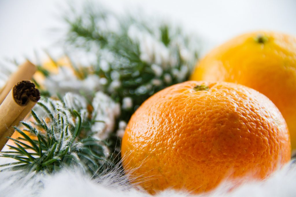 cinnamon sticks, pine, and mandarins on snowy background
