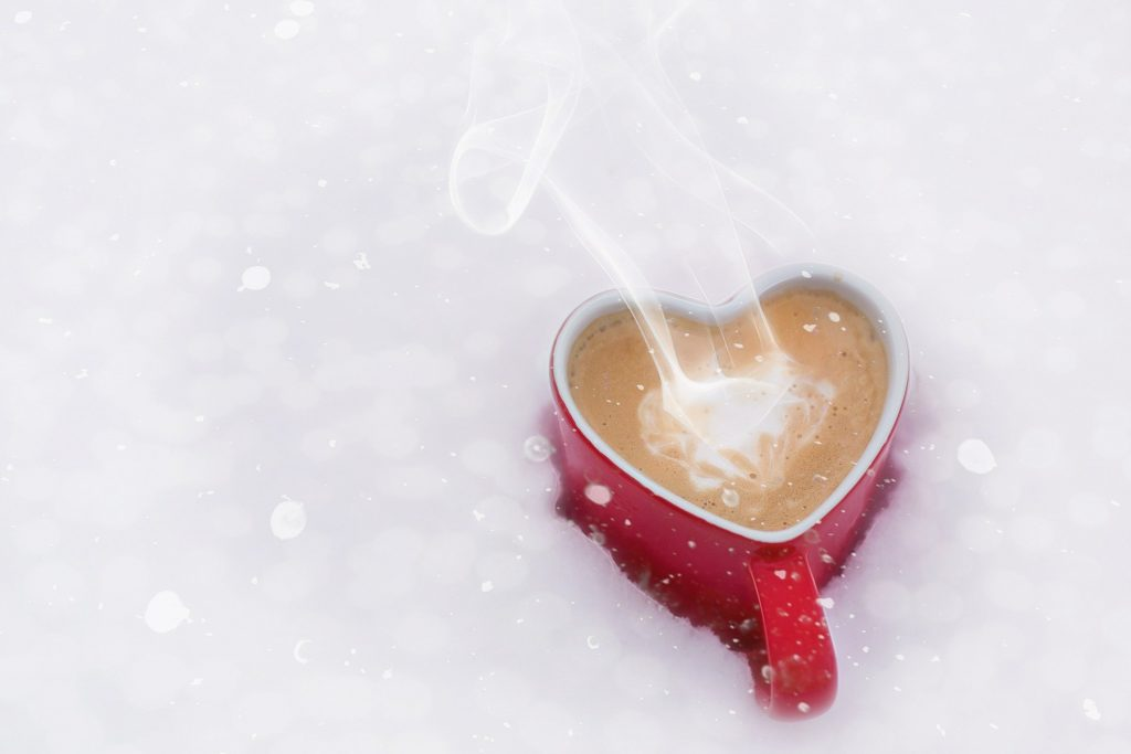 red heart-shaped mug of coffee in the snow