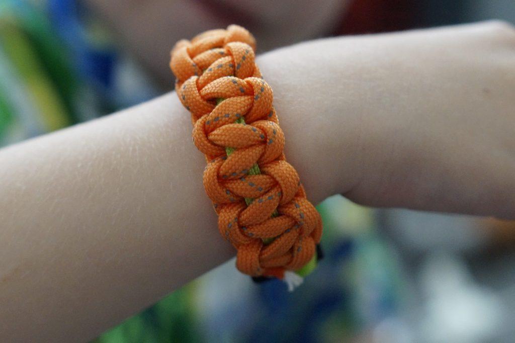 orange paracord bracelet on a wrist