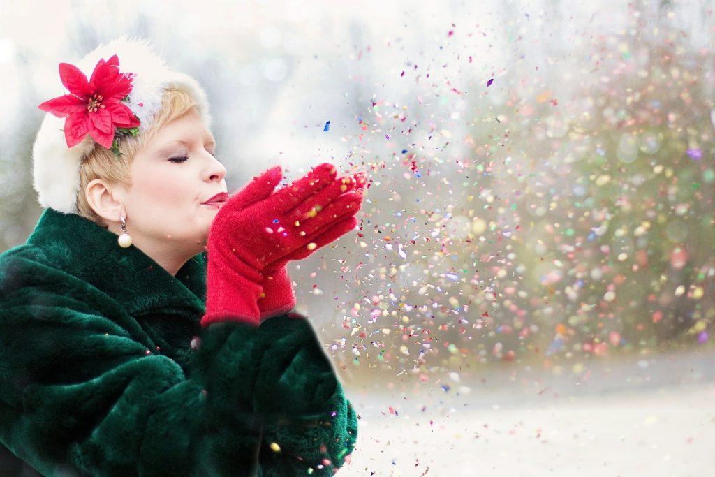 Woman wearing red gloves blowing Christmas glitter