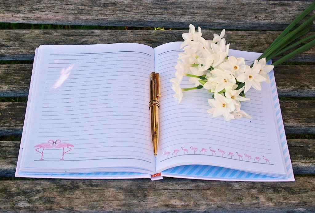 open journal with a gold pen and white flowers