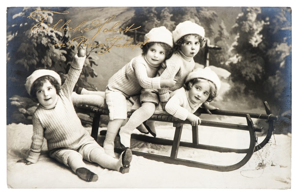 1910: old photo of kids with sled. nostalgic vintage christmas postcard from ca. 1910, in Berlin, Germany
