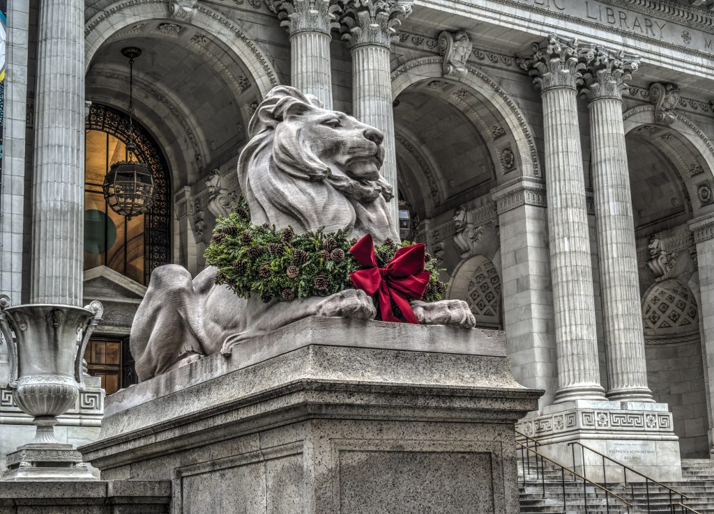 Lion statue, wearing Christmas wreath around neck, in front of Library of the New York Public Library,
