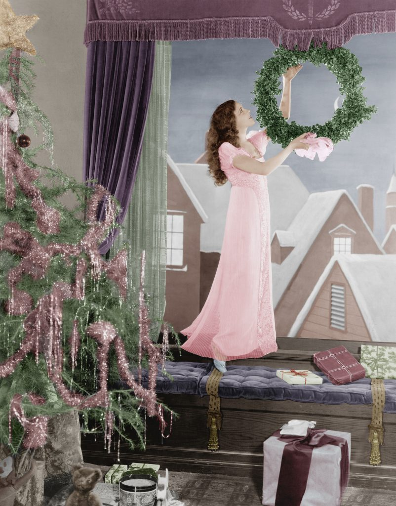 Woman in a long pink dress hanging a Christmas wreath in a window with snowy rooftops outside